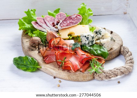 Sliced prosciutto with salami,cheese and basil on a wooden board - stock photo