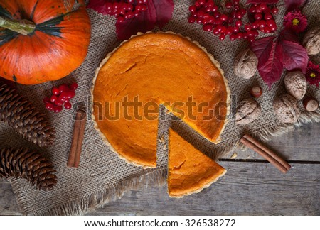 Sliced pumpkin tart cake sweet dessert with cinnamon, nuts and autumn composition on vintage table background. Rustic style and natural light - stock photo