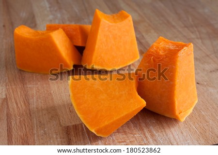 Sliced raw orange pumpkin on wooden cutting board - stock photo