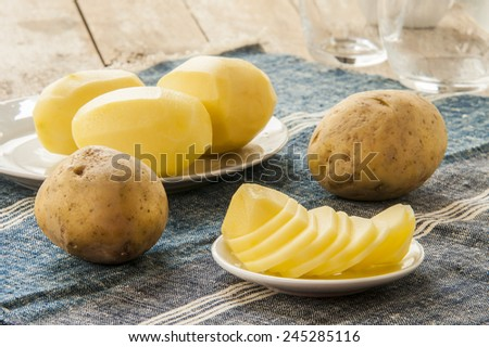 sliced raw potato on kitchen table - stock photo