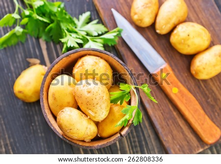 sliced raw potato on the kitchen table - stock photo