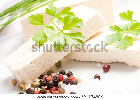 sliced raw tofu with spices on white plate, close up - stock photo
