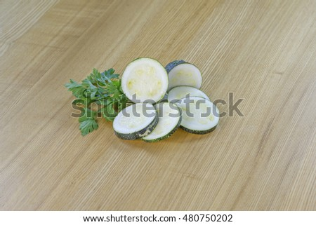 Sliced raw zucchini with parsley on wooden
