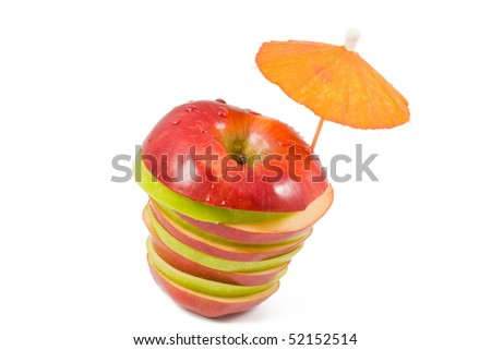 sliced red and green apple with a cocktail umbrella on a white background