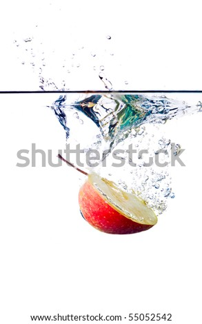 Sliced red apple falling into water isolated on white - stock photo