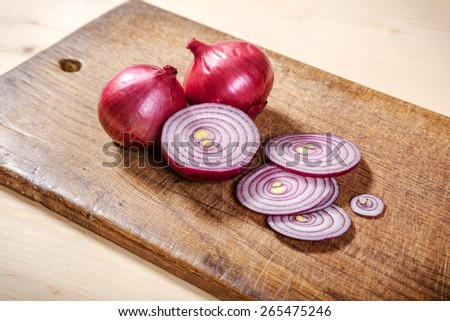 sliced red onion on wooden cutting board - stock photo