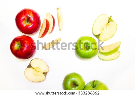 sliced rings of ripe apples in different colors on a white background
