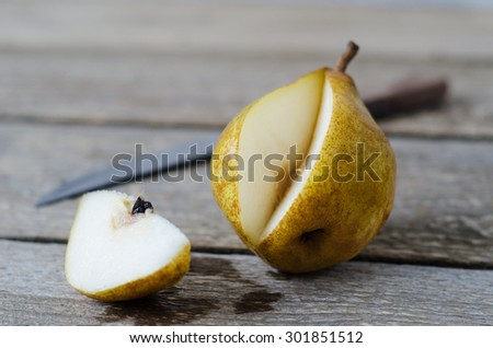 sliced ripe pears on a wooden table with knife - stock photo
