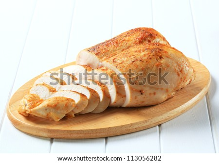 Sliced roast chicken breasts on cutting board  - stock photo