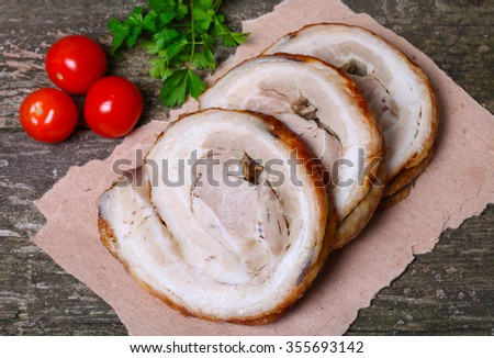 Sliced roasted roll pork loin with spices and fresh vegetables on a wooden background. - stock photo