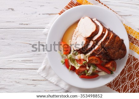 Sliced roasted turkey breast and fresh vegetables on the plate. Horizontal top view