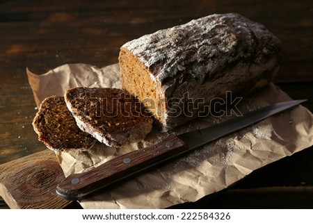 Sliced rye bread and knife on craft paper on cutting board on wooden background - stock photo