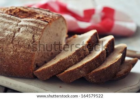 Sliced rye bread on cutting board closeup - stock photo