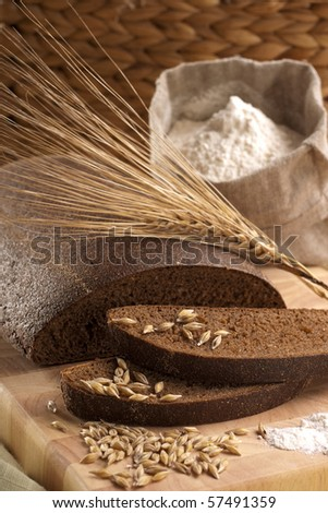 Sliced rye bread with flour and grains - stock photo