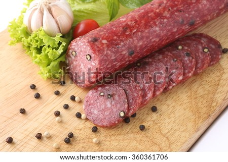 Sliced salami isolated with herb on a white background - stock photo