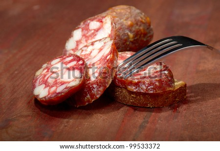 Sliced salami  on rustic wooden table, selective focus - stock photo