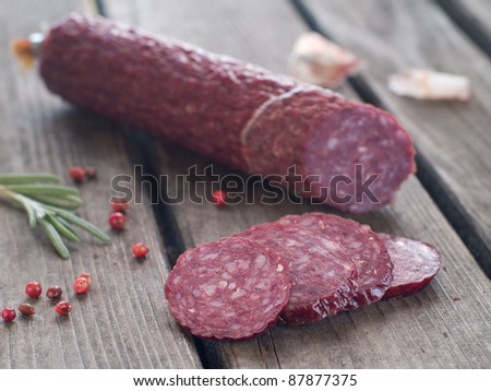 Sliced salami with pepper and rosemary on rustic wooden table, selective focus - stock photo