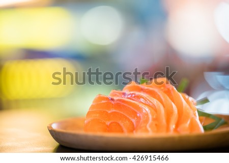 Sliced salmon sashimi served on wooden platter, Japanese food delicious menu, bokeh background with copy space - stock photo