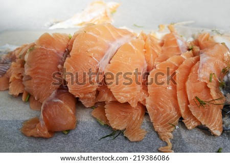 sliced salted salmon fillet on paper, horizontal - stock photo