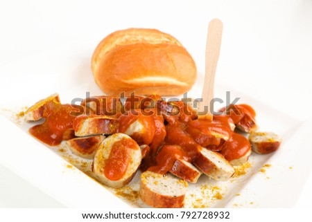 sliced sausage with curry sauce and a roll