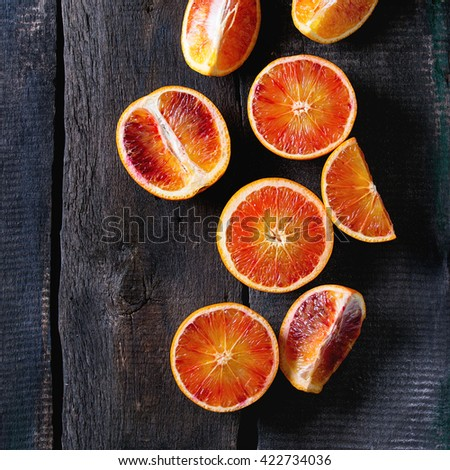Sliced Sicilian Blood oranges fruits over old dark wooden background. Top view. Square image - stock photo