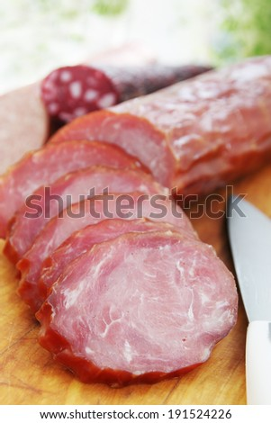 sliced smoked sausage on a wooden board