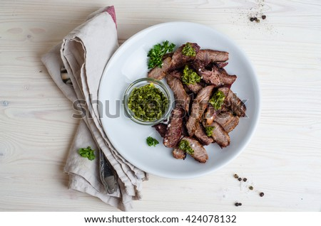 Sliced Steak served in white bowl with chimichurri sauce. Top view. - stock photo