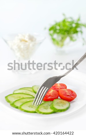 Sliced tomato and cucumber on a plate.