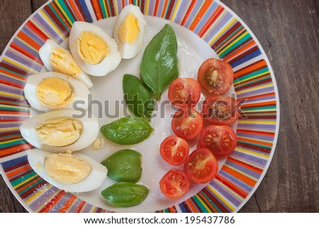 Sliced tomatoes cherry eggs and basil on plate, closeup