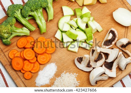 Sliced vegetables an spice on wooden cutting board. Top view - stock photo