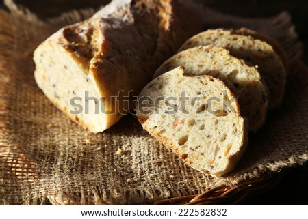 Sliced white bread on sackcloth napkin on wicker basket on wooden background
