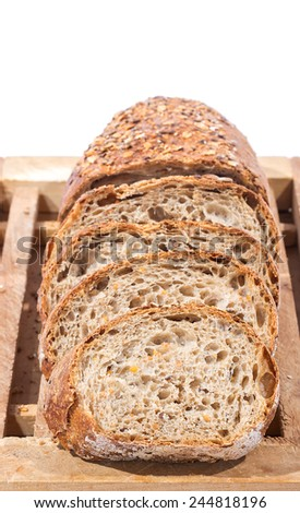 Sliced Whole Grain Bread on Wooden Cutting Board over white background - stock photo