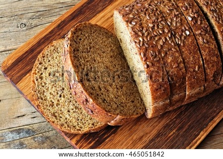 Sliced whole grain bread with nutritious flax seeds, above view on wooden board