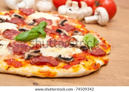 sliced whole salami and mushrooms pizza with ingredients  on a wooden table - stock photo