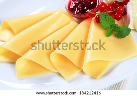 Sliced yellow cheese and red currant sauce