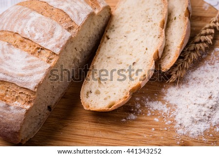 slicedof fresh bread on brown wooden table - stock photo