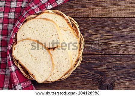 Slices bread in wicker plate on vintage wooden table with copy space - stock photo