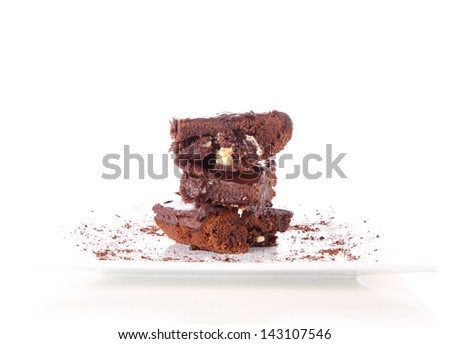 Slices of a brownie with white chocolate chunks on a plate decorated with cocoa - stock photo