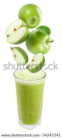 Slices of apple falling into a glass of fresh juice - stock photo