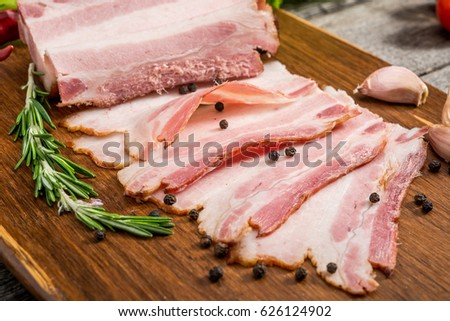 Slices of bacon on the wooden background. Brisket