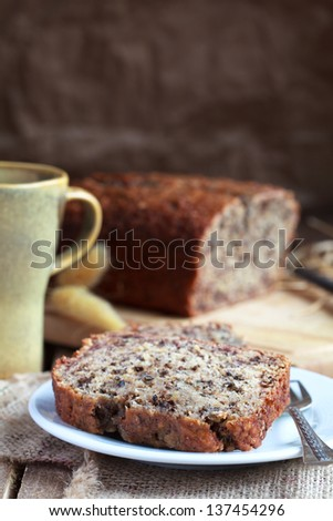 slices of banana bread with nuts in the white plate with a loaf of bread in the background - stock photo