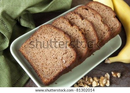 Slices of banana bread, with whole bananas and walnuts. - stock photo