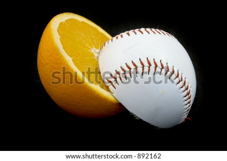 slices of baseball ball and orange on black background - stock photo