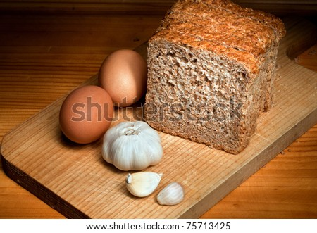 slices of bread, garlic and eggs on a wooden table - stock photo