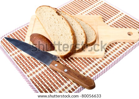 Slices of bread  knife chopping board on a white background