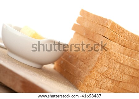 Slices of bread with bowl of butter on the side