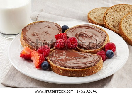 Slices of bread with chocolate cream, fresh berries and glass of milk