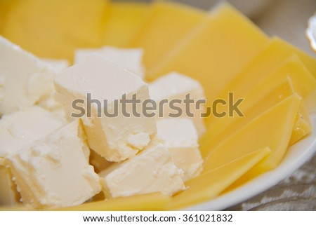slices of cheese and cubes of feta on the plate - stock photo