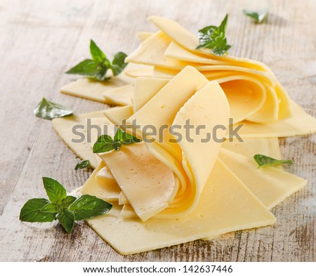Slices of cheese with fresh herbs. Selective focus - stock photo