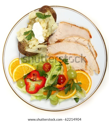 Slices of cold roast turkey with a baked potato and a salad with vegetables and fruits, a great way to use up the festive leftovers - stock photo